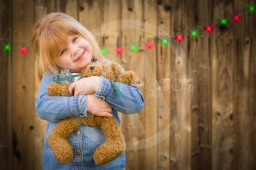 Girl Holding Teddy Bear In Front of Wooded Background...