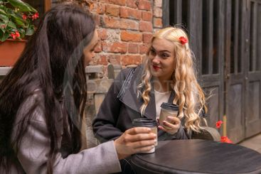girl in surprise listens to her friend on a bench with...