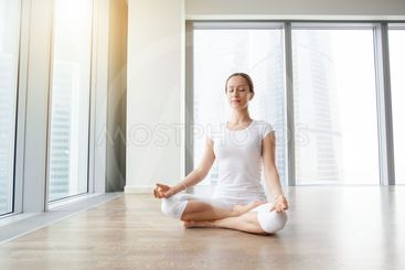 Young attractive woman in Ardha Padmasana pose against...