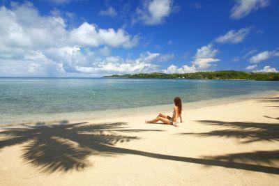 Young woman in bikini sitting on a tropical beach,...