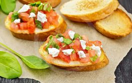 Bruschetta with tomato and cheese on table