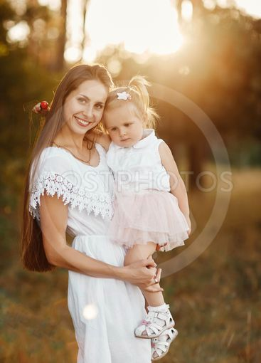 little girl with two tails. a woman holds a child in her...