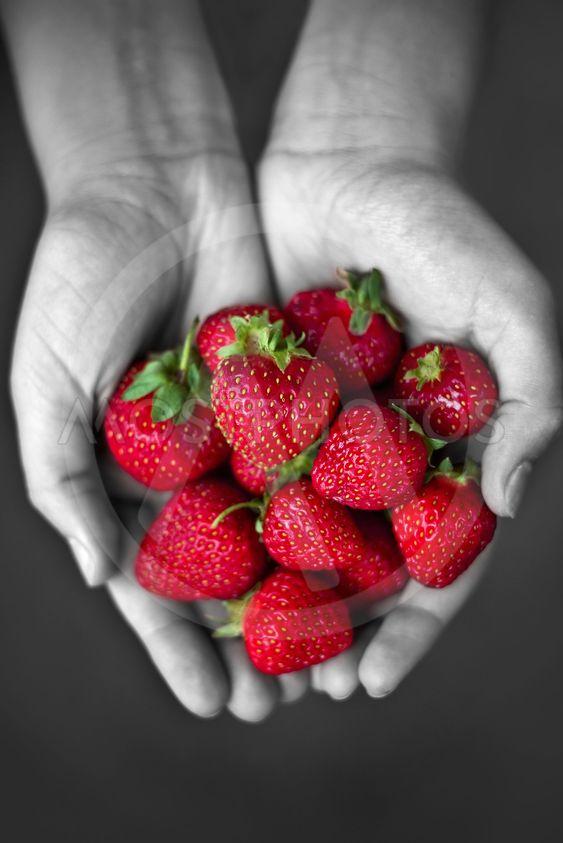 Händerna fulla av jordgubbar