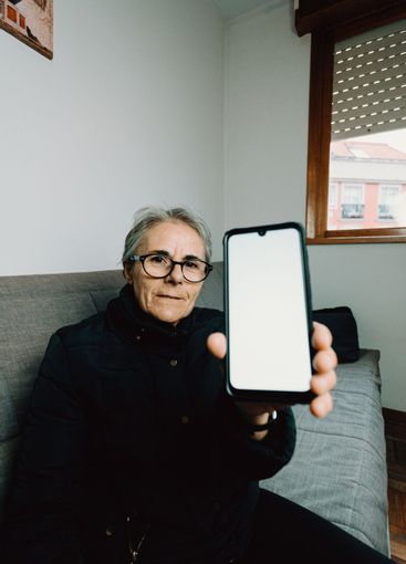 Old woman showing a mobile phone with a white screen...