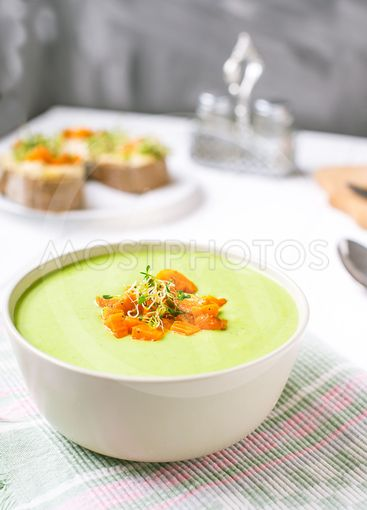 Bowl of Green peas cream soup with baked carrot and...
