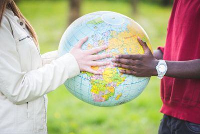 Multiracial Teen Couple Holding Globe Map