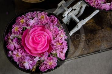 Pink Roses with rose candle on a container