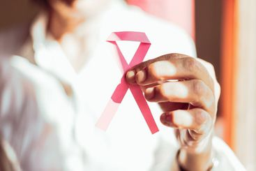 A old woman showing a pink ribbon