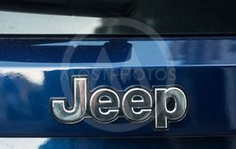 Jeep logo on blue car rear parked in the street