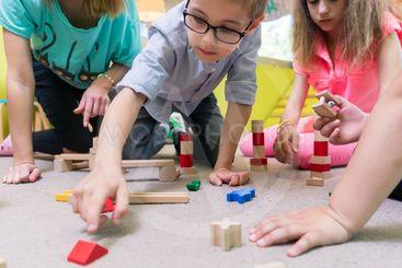 Female educator teaching children to build a train...