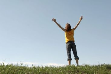 The girl stands at top of a hill
