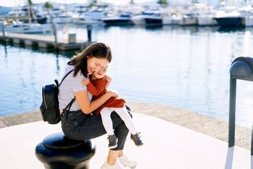 Young woman is hugging her daughter tight while sitting...