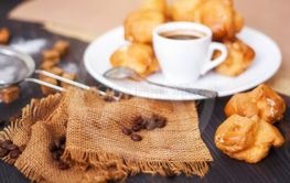 Cup of hot black coffee with home made profiteroles on a...