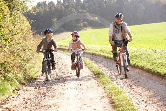Young father with children ride bikes in park
