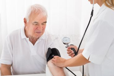 Female Doctor Checking Blood Pressure Of Male Patient