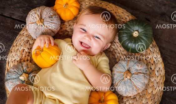 happy baby on the basket with different pumpkins