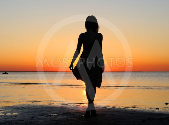 Woman as silhouette by the sea