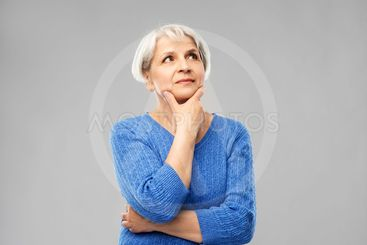 portrait of senior woman in blue sweater thinking