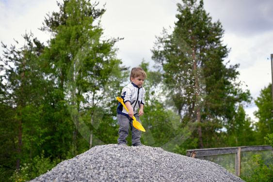 Little boy plays on heap of crushed stone