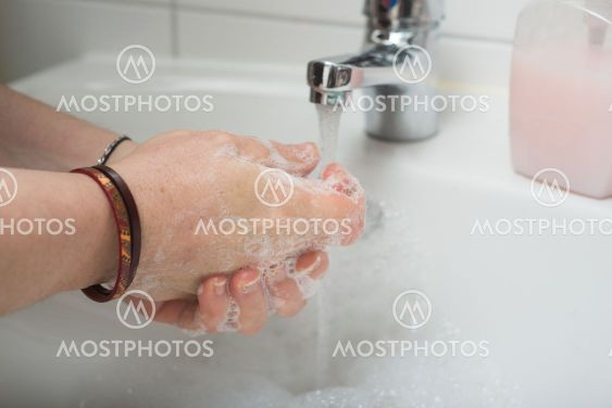 hands of woman whashing hands to protect against the...