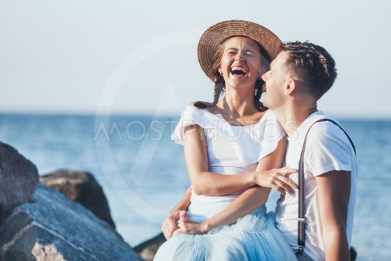 Happy young romantic couple relaxing on the beach and...