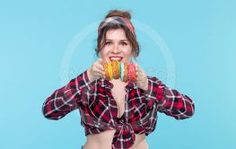 Cheerful beautiful young woman in a plaid shirt holds in...