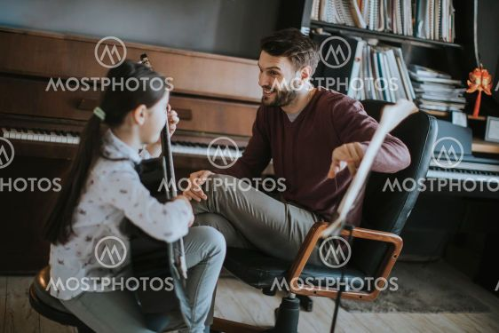 Little girl playing guitar with her music teacher in the...