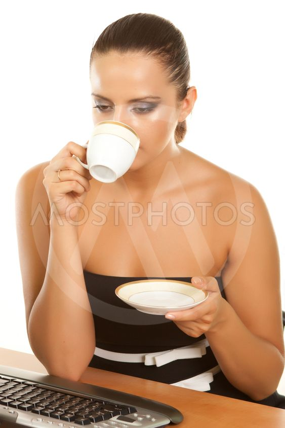 young woman holding a cup of coffee at her workplace