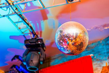 Big disco ball on a colored background in a nightclub