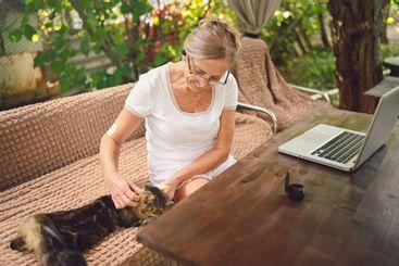 Happy senior woman with home cat use wireless headphones...