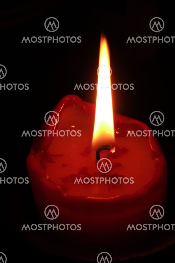 Burning candle, black background