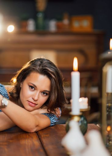attractive brunette lay down on wooden table with candle...
