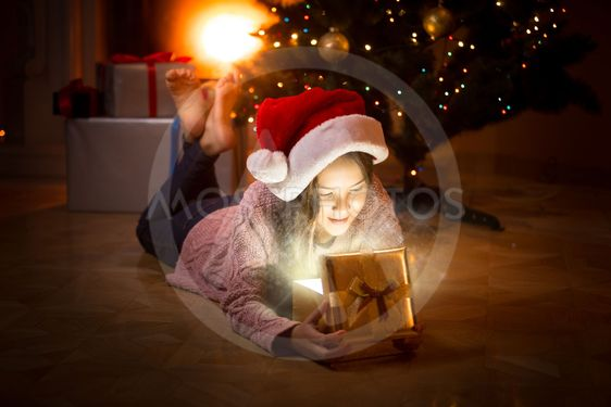 happy girl lying on floor and looking inside of magic...