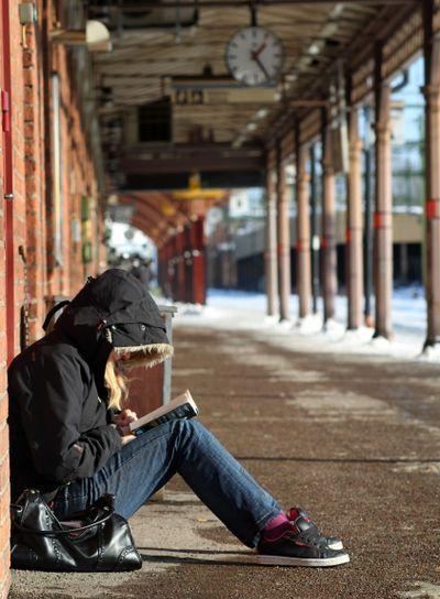 Resenär läser i väntan på tåget 1