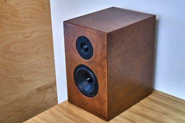 Wooden bookshelf speaker standing on a table against the...