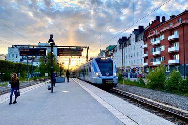 Människor på perrong med inkommande tåg i solnedgången.