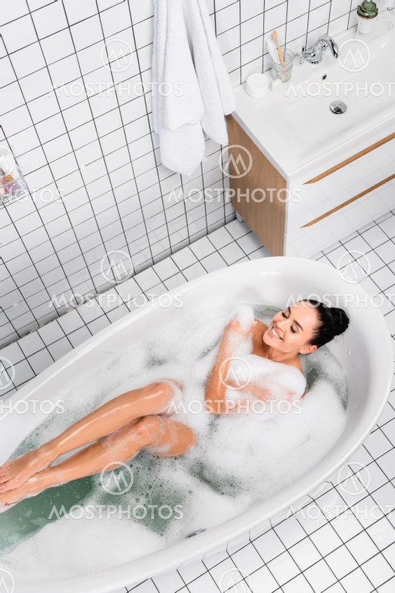 Top view of cheerful woman with closed eyes enjoying in...
