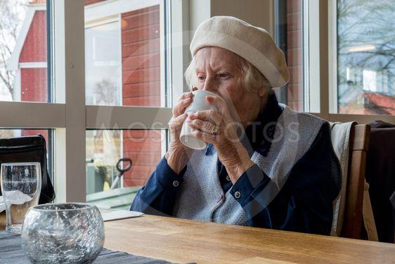 Äldre kvinna dricker kaffe efter maten.