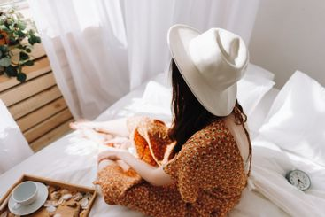 Beautiful young woman in white hat sitting on bed near...