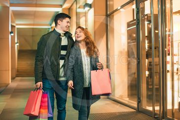 The happy couple with shopping bags enjoying night at...