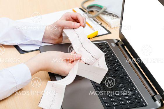 physician examines patient electrocardiogram