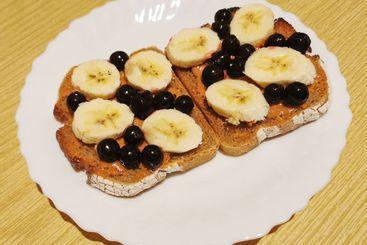 Dark bread, peanut butter, black currant, banana slices
