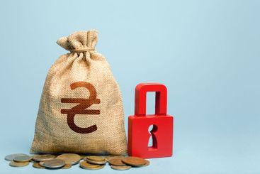 Ukrainian hryvnia money bag and red padlock. Tight...