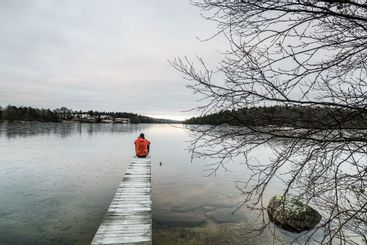 Lonely man sitting on jetty, Sweden.