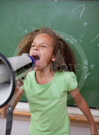 Portrait of a cute schoolgirl screaming through a megaphone