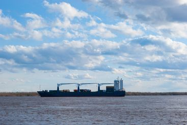 Cargo ship on the river against the blue sky in lush...