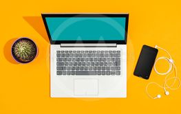 Laptop and smartphone on a bright yellow desk