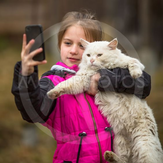 Little girl photographs herself with a stray cat on the...