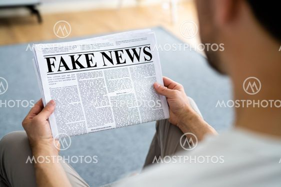 Businessman Reading Fake News Article On Newspaper