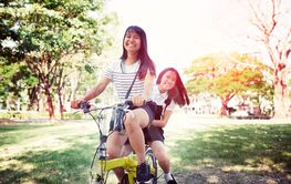 cheerful asian teenager riding bicycle in pulbic park